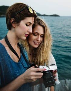 Two women ocean SLR camera