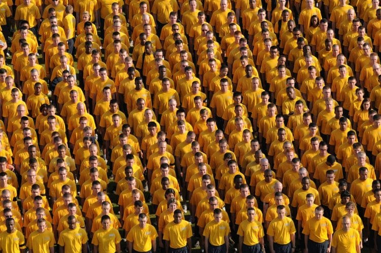 community of people standing in yellow shirts